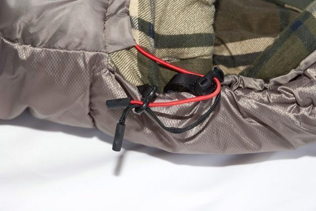 Затяжки капюшона - плоский шнур затягивает верх, а круглый низ. Разная форма позволяет определить нужную затяжку на ощупь. Кемпинговый спальный мешок большого размера Alexika Siberia Wide Plus