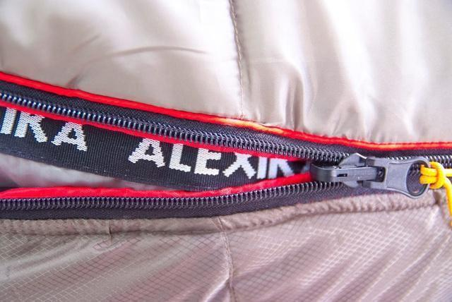 Стропа от закусывания ткани замком молнии и валик, не позволяющий проникать холодному воздуху сквозь молнию. Туристический спальный мешок для низких температур Alexika Aleut Compact
