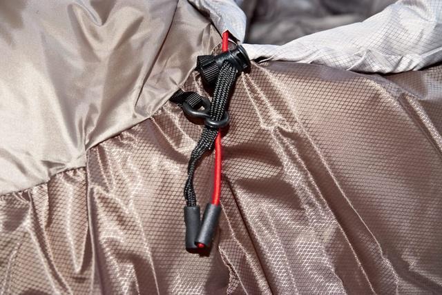 Затяжки капюшона - плоский шнур затягивает верх капюшона, а круглый - низ. Разная форма позволяет определить нужную затяжку на ощупь. Пластиковый крючок фиксирует затяжку на внешней стороне капюшона.. Спальный мешок для зимнего туризма Alexika Iceland