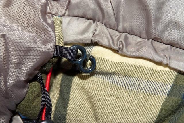 Затяжки капюшона фиксируются крючком на внешней стороне спального мешка, чтобы при перевороте на бок шнуры не ложились на лицо. Кемпинговый спальный мешок большого размера Alexika Siberia Wide Plus