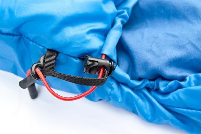 Затяжки капюшона - плоский шнур затягивает верх, а круглый низ. Разная форма позволяет определить нужную затяжку на ощупь. Кемпинговый спальник-одеяло Alexika Comet